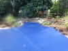 Dark Blue debris pool cover for pool with rocks