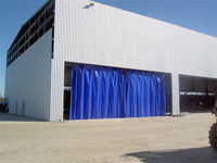 a picture of an industrial warehouse curtain that closes protects a work area from the weather