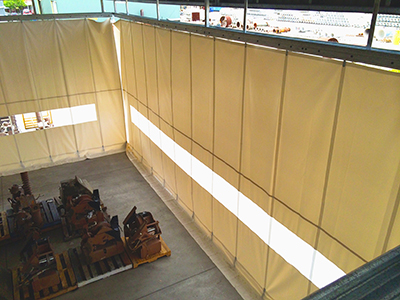 a picture of an industrial warehouse curtain that closes in a sand blasting area
