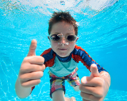 image of a boy in a swimming pool giving two thumbs up